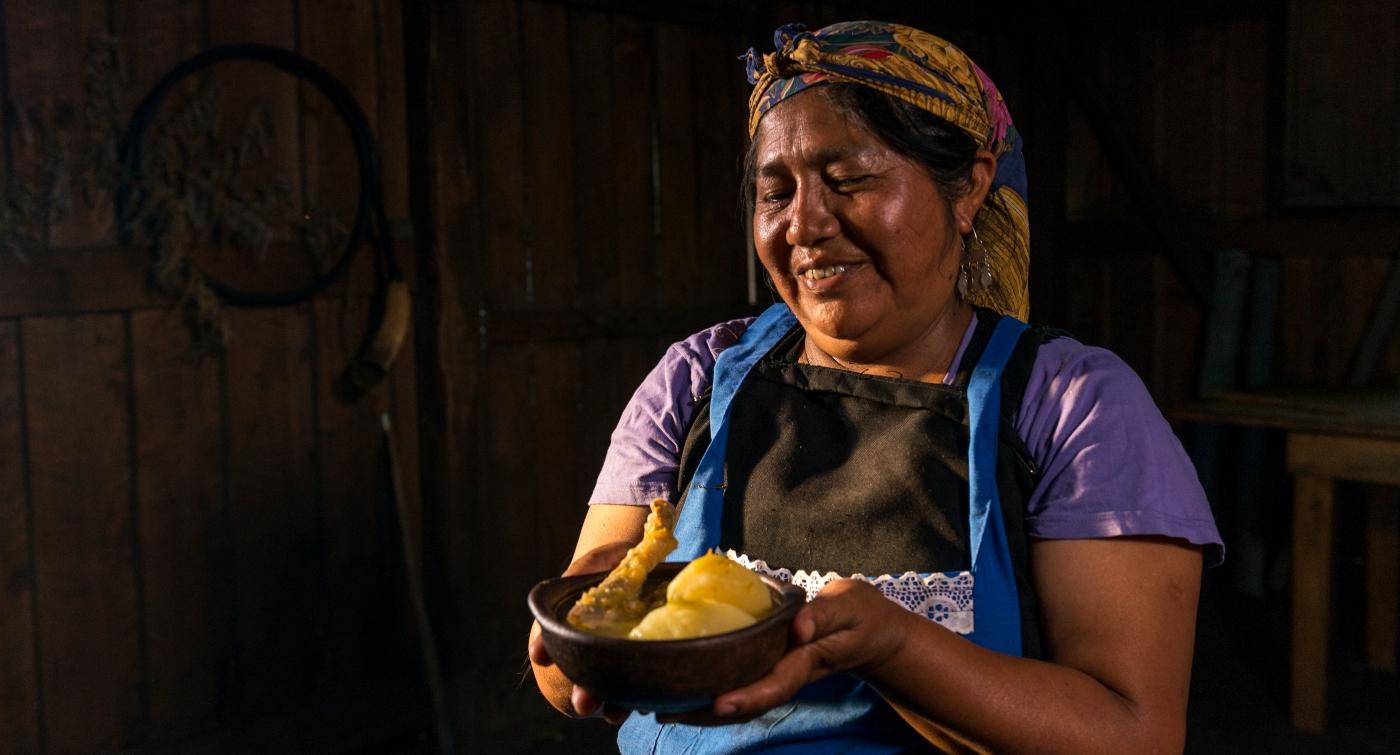 Imagen de una mujer mapuche con una cazuela tradicional en sus manos