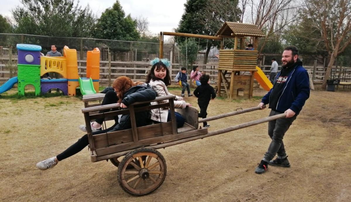 Imagen de un padre jugando con sus dos hijas en una granja