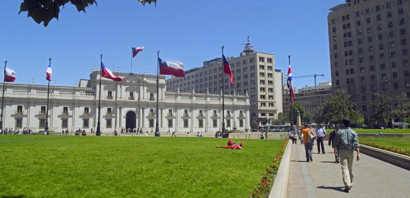 imagen panorámica del Palacio de La Moneda rodeado de banderas chilenas flameando