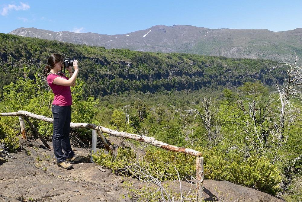 Valle Las Trancas y una mujer observando la naturaleza desde un mirador en la Reserva nacional Ñuble