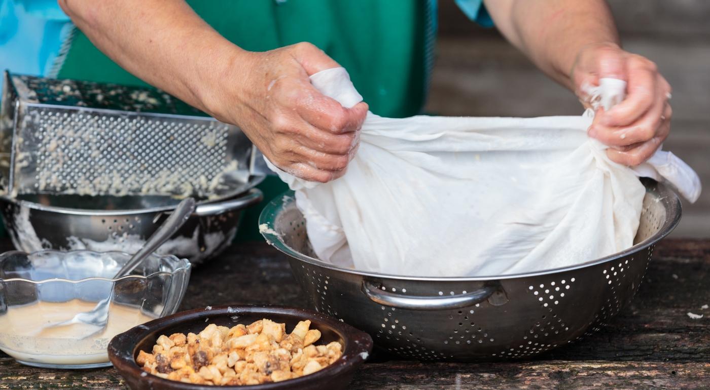 Imagen de las manos de una mujer chilota cocinando milcao