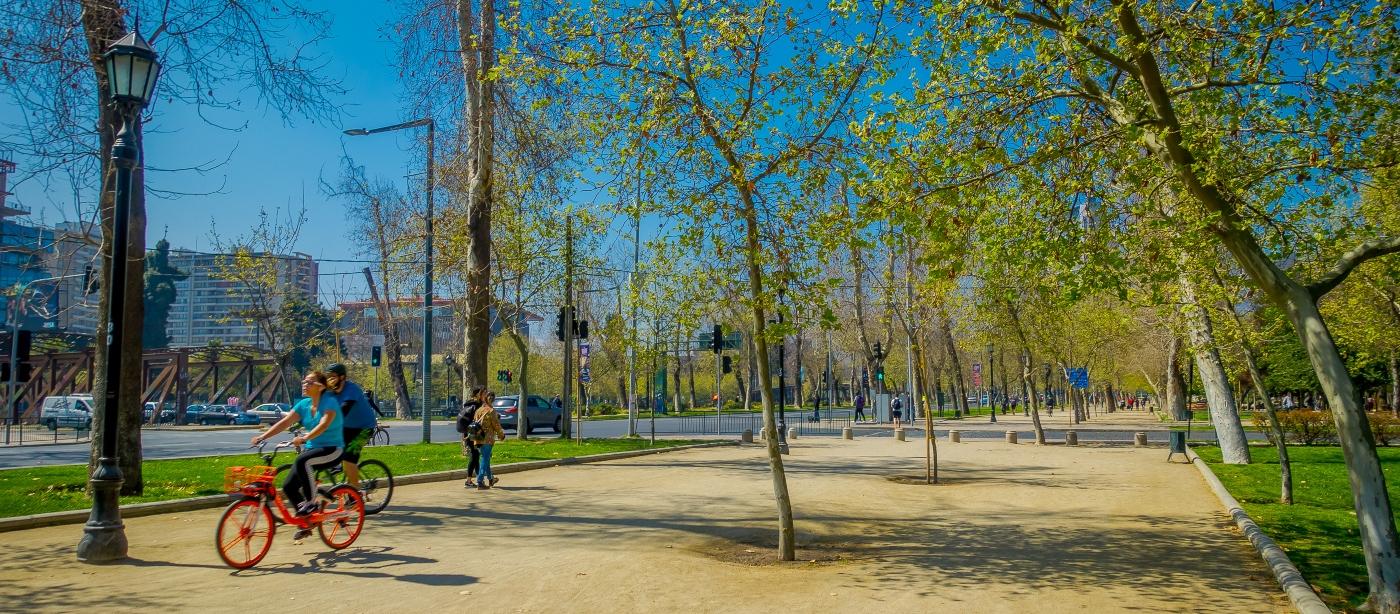 Imagen de gente andando en bicicleta en el parque forestal de santiago