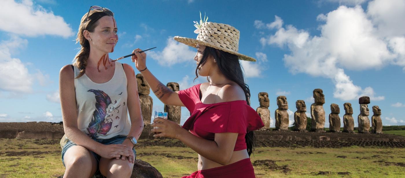Imagen de una mujer pintándose formas tribales en su cuerpo en Rapa Nui