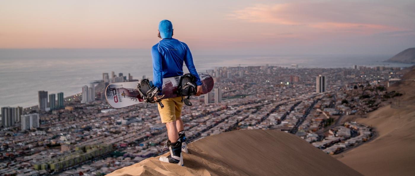 Imagen d euna joven admirando la vista desde la cima de una duna de arena en el norte de Chile