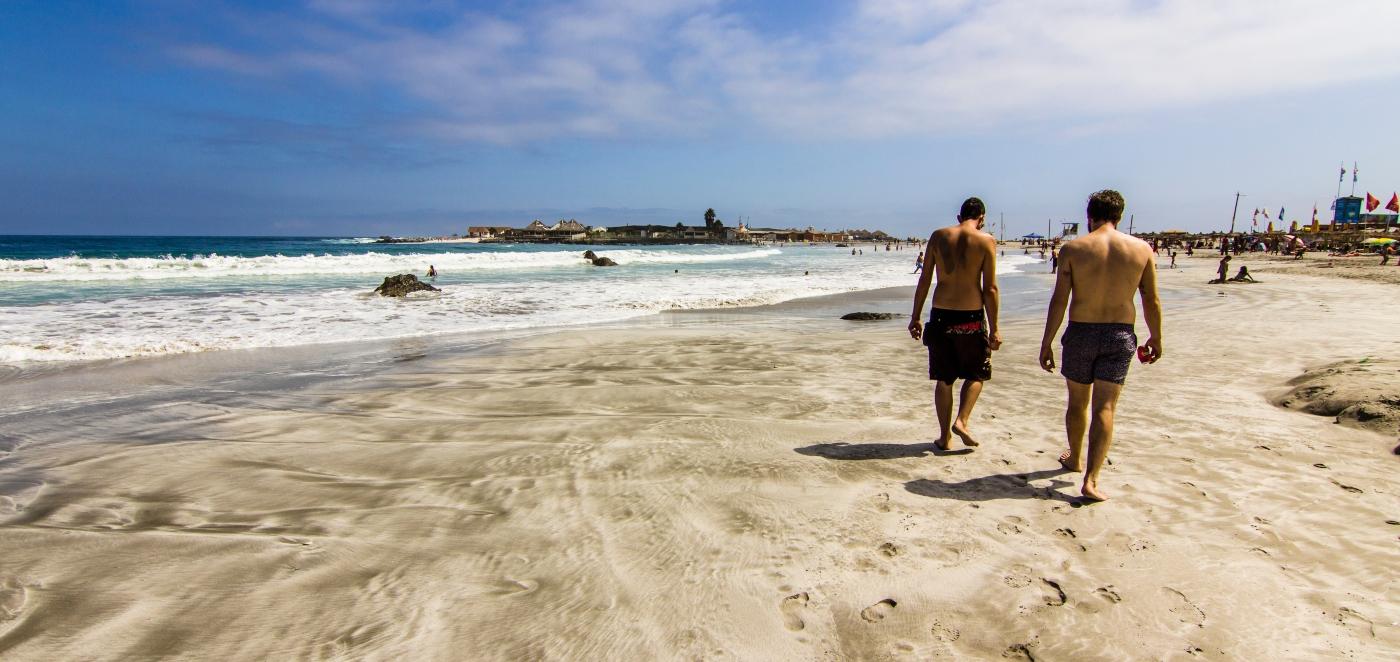 Imagen de dos hombres caminando por la orilla de la playa Totoralillo