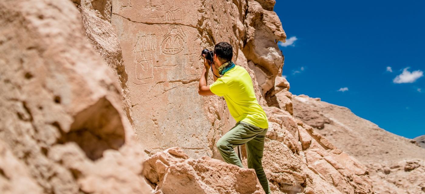 Imagen de un hombre fotografiando petroglifos
