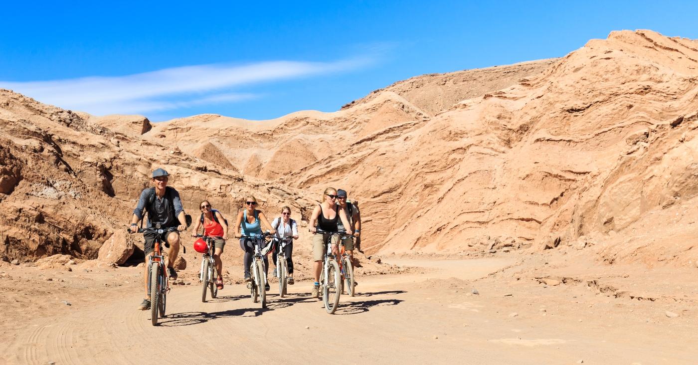 imagen de un grupo de turistas recorriendoe l desierto de Atacama en bicicleta