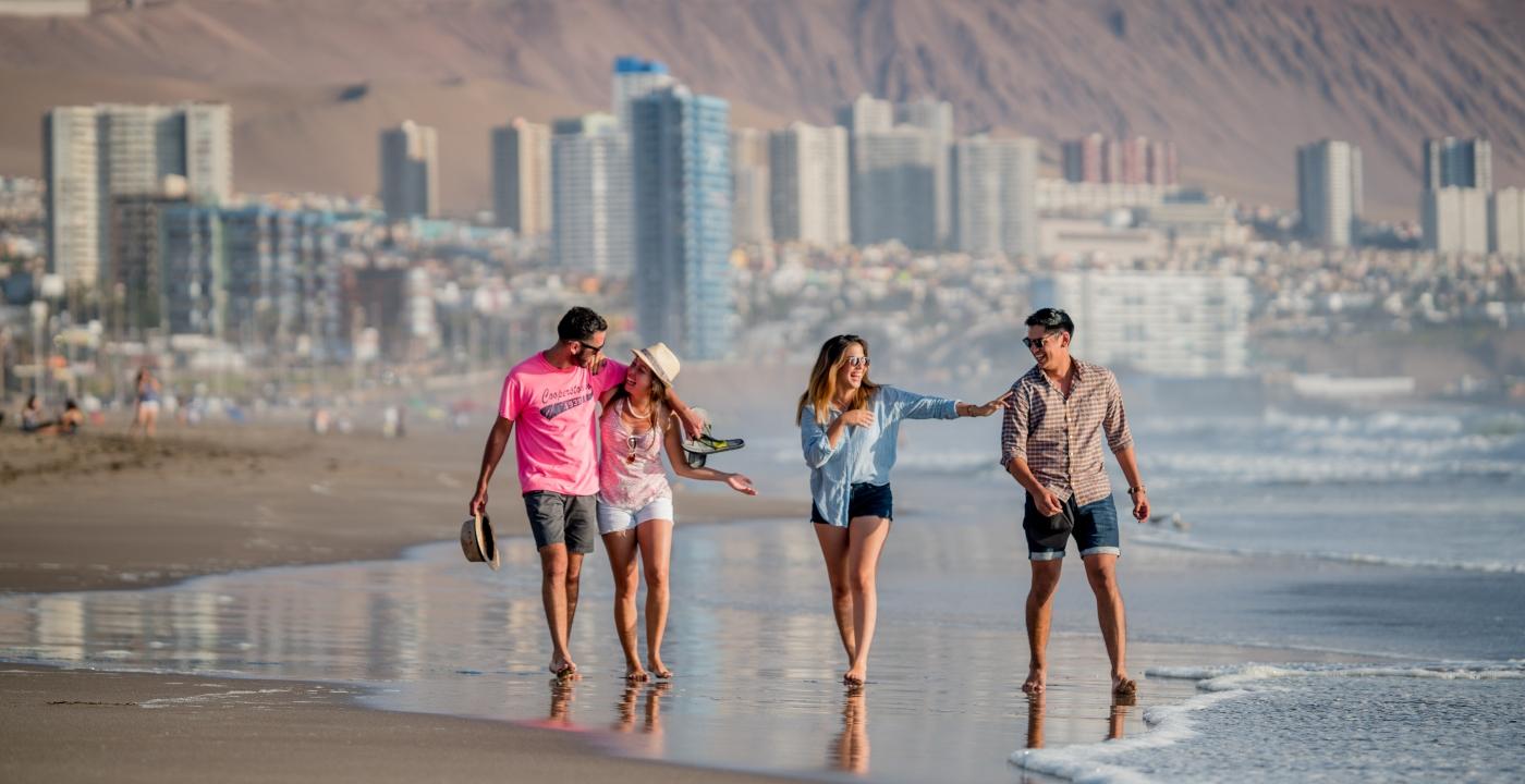 Imagen de dos parejas de turistas caminando por las playas de Iquique