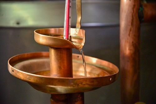 Alambique de cobre destilando el alcohol del vino