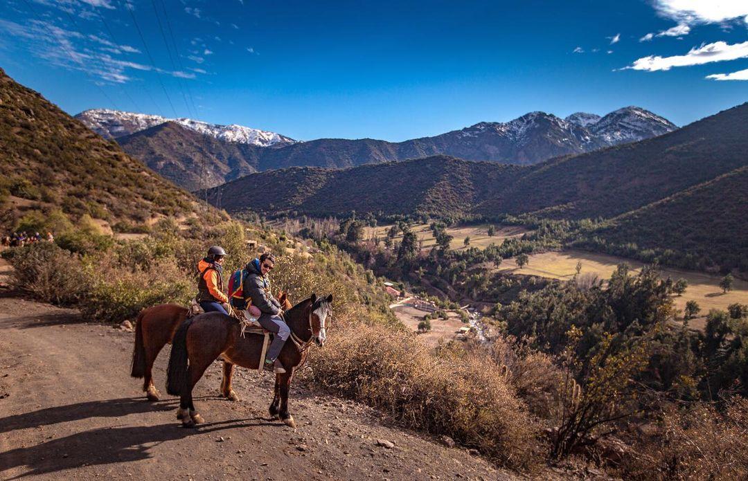 Personas a caballo contemplando el paisaje en Farellones