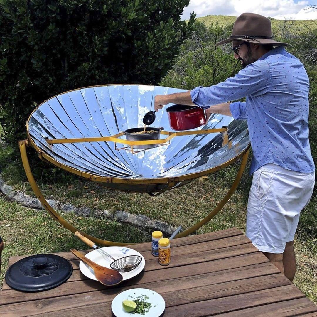 Hombre cocinando en cocina solar