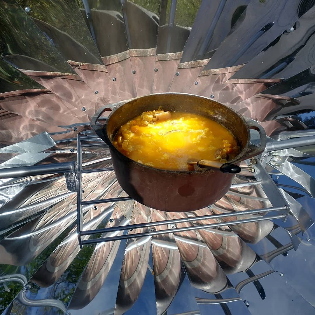 Olla con sopa siendo cocinada en cocina solar