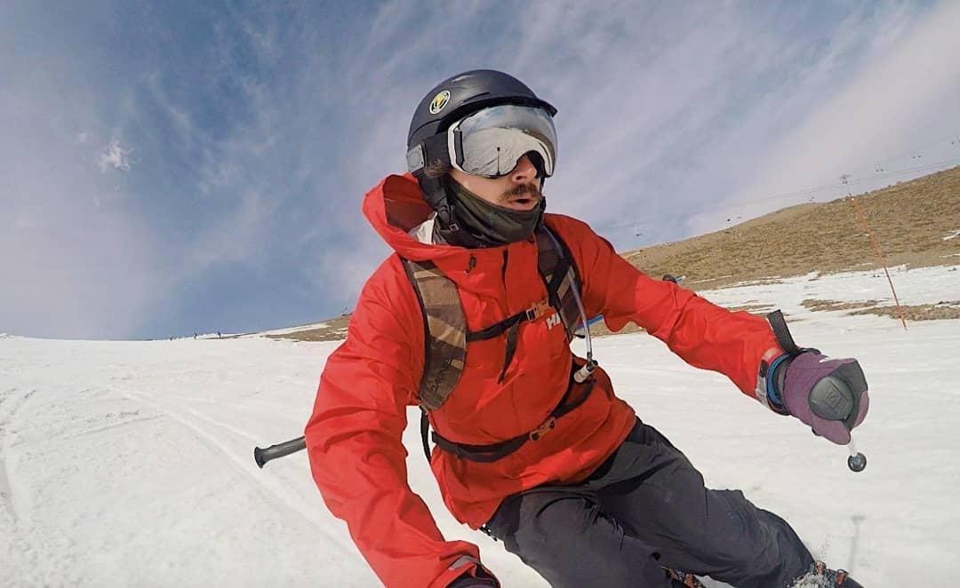 Hombre con todos sus implementos esquiando montaña abajo