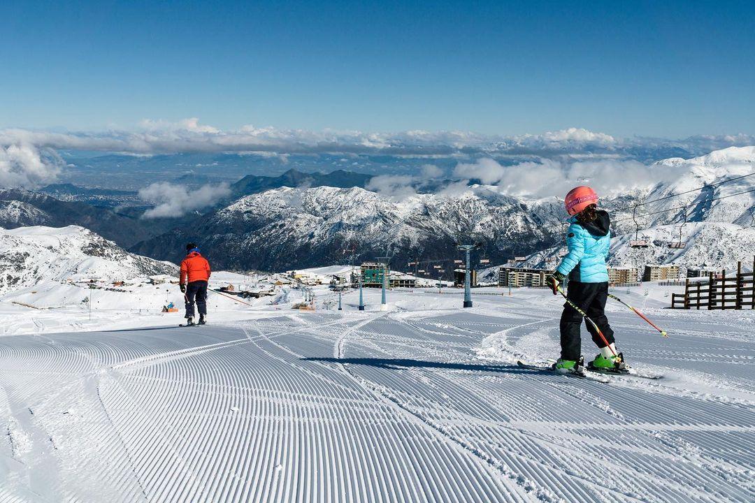 Personas esquiando desde lo alto de la montaña con vista a la cordillera nevada