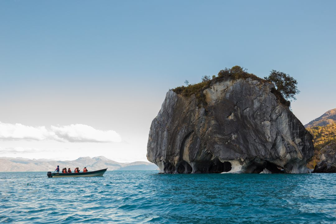 Tourists contemplating the Marble Chapels in Aysén from a boat.