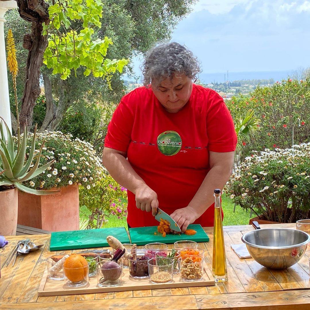 Mujer Chef cocinando al aire libre con alimentos de la huerta