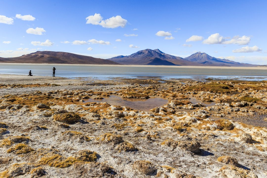 Two people in the immensity of the Surire Salt Flat in the North of Chile