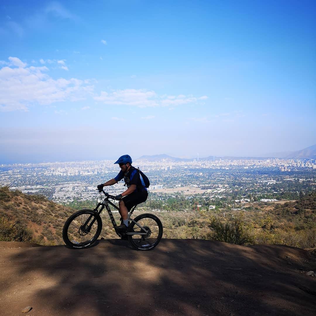 Ciclista en lo alto del parque Mahuida con la ciudad de Santiago al fondo