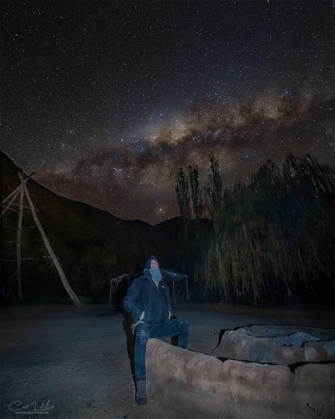 Hombre mirando las estrellas en camping Río Mágico, Cochiguaz
