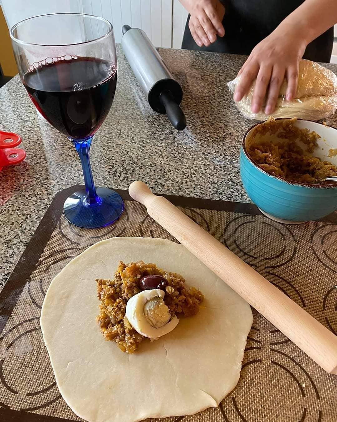 Masa de la empanada con relleno de pino y una copa de vino tinto