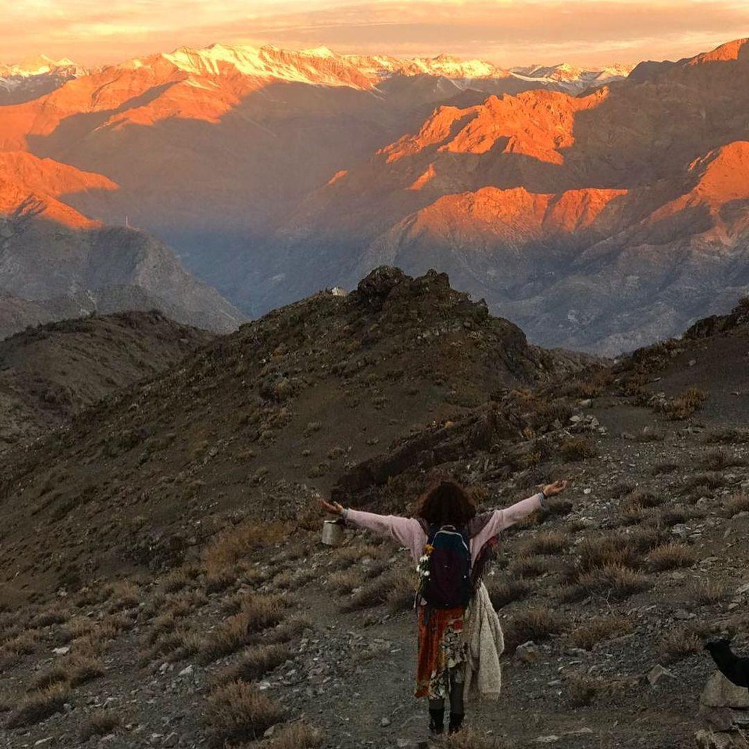 Mujer con brazos abiertos recibiendo energía de la cordillera de Los Andes, Chile