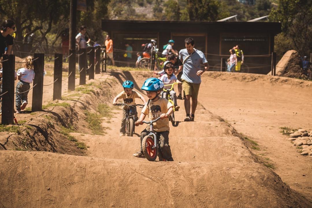 Kids riding their bikes over dirt jumps