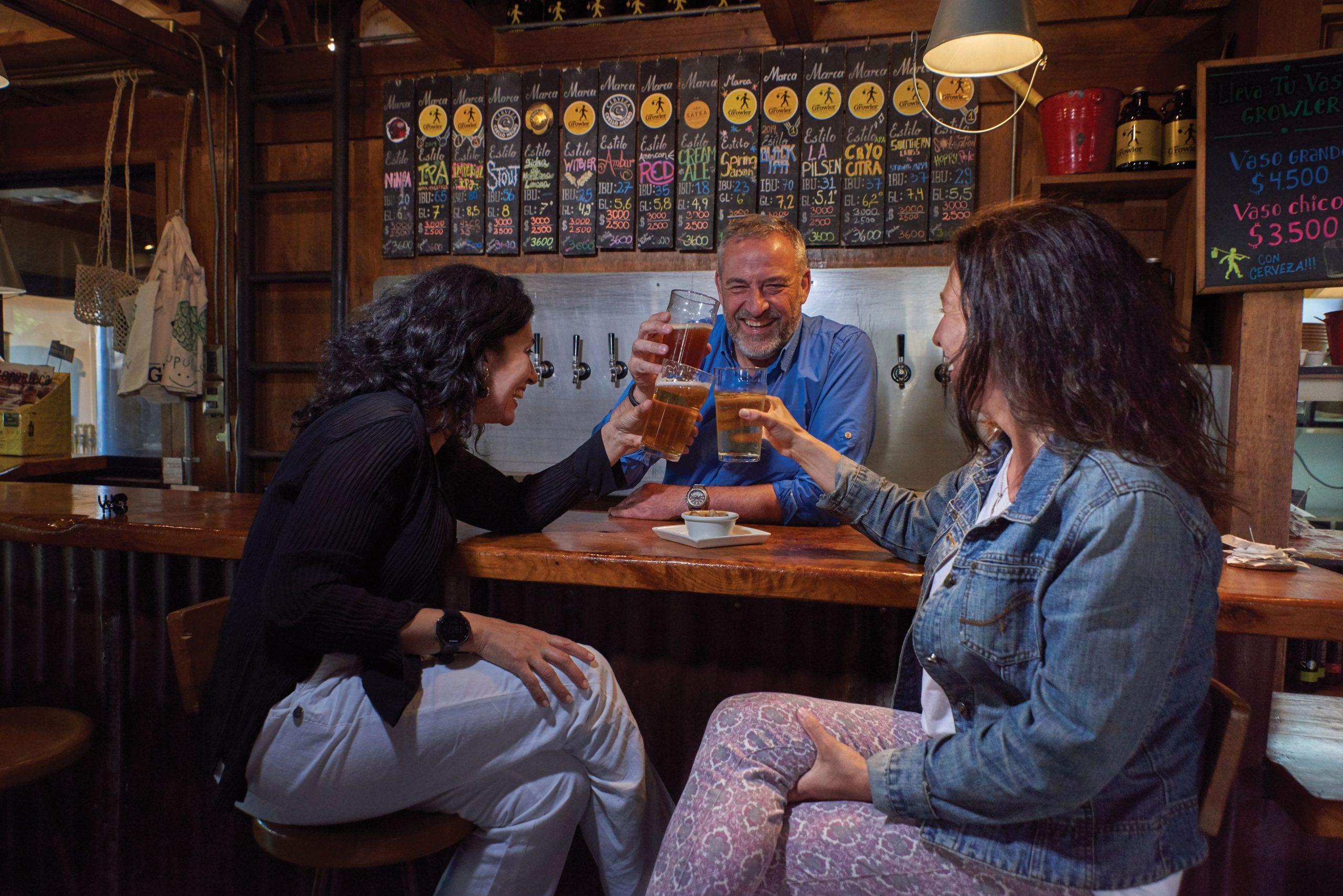 Tres amigos riendo mientras beben cerveza artesanal, Valdivia, sur de Chile