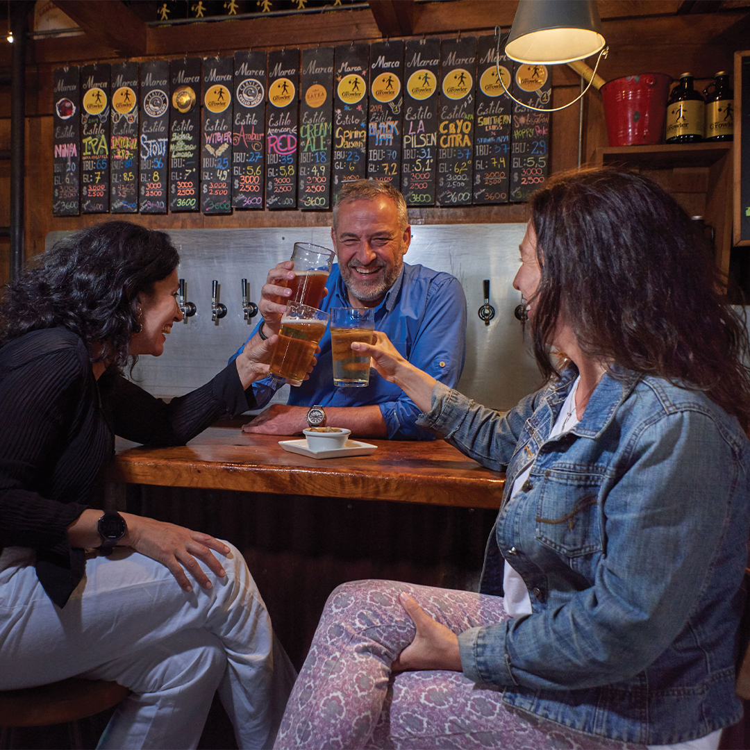 Friends making a toast with craft beer at a bar in Valdivia, southern Chile