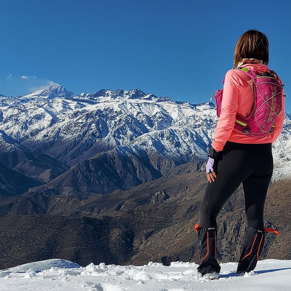 Mujer en la nieve observando el monte Aconcagua frente a ella.