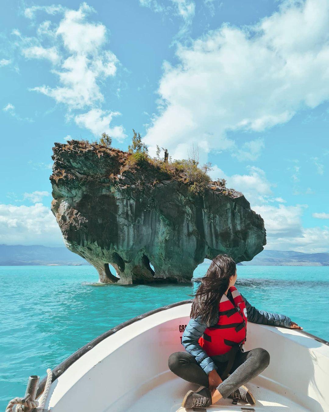 Mujer en bote en dirección hacia una Capilla de Mármol, sur de Chile