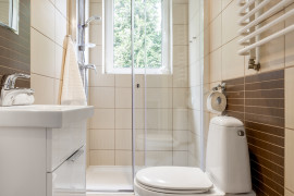 Small bathroom interior in brown with window, toilet, shower and basin