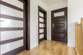 Light home corridor with wooden doors and brown floor