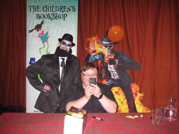 Derek Landy takes a selfie with a fan dressed as Skulduggery Pleasant
