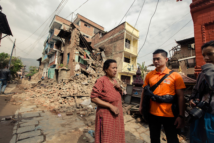 CHC pastor Kenneth Sim (in orange) listens as a Nepalese quake victim describes how she lost her house in the quake.