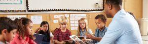 Elementary school class sitting cross legged using tablets