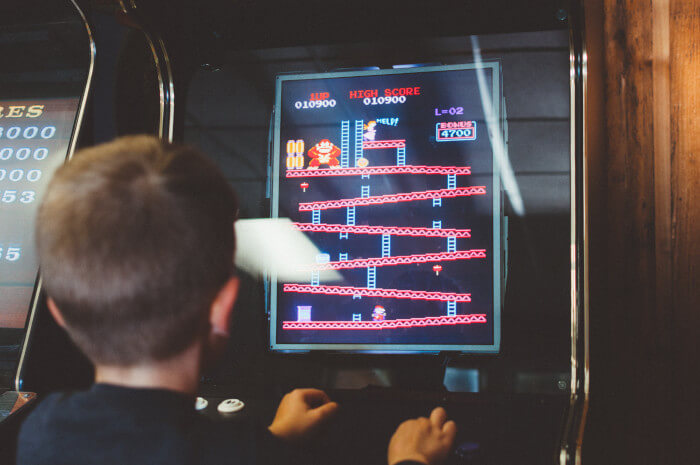 kid playing an old school arcade game