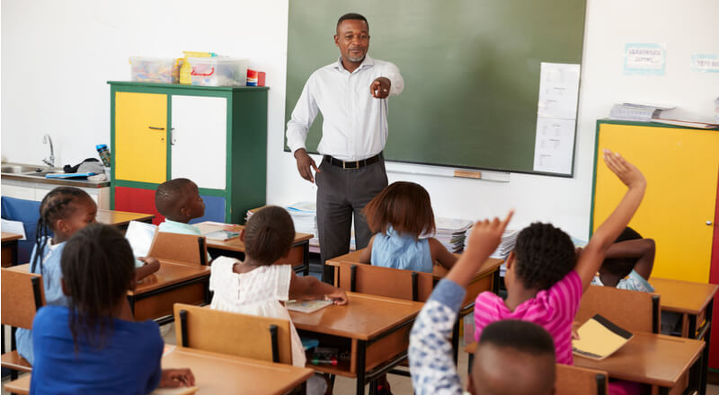 Teacher and kids with hands up in an class