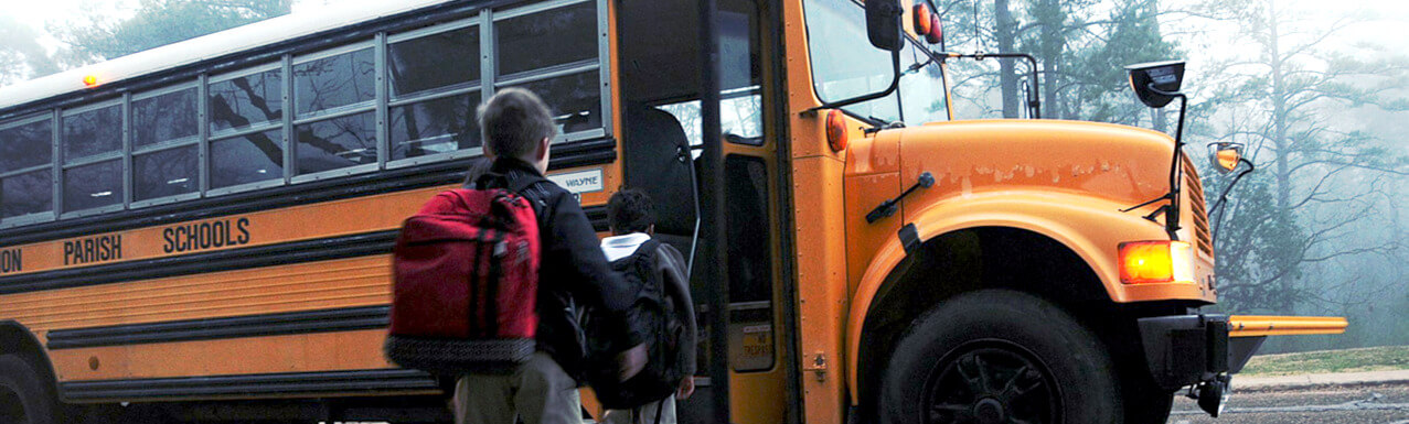Kids getting into a yellow school bus