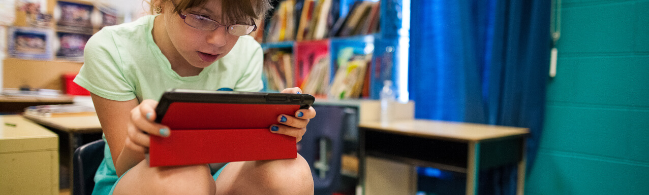 Girl student seated on the top of her chair in class looking at her tablet