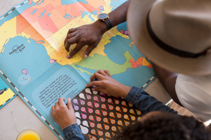 Kid learning on a map with an adult