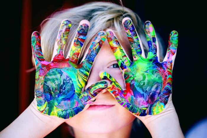 Kid with multicolour paint on his hands