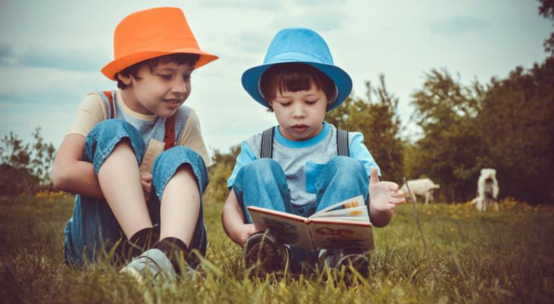 2 boys reading in a field