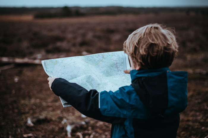 child looking at a map outside