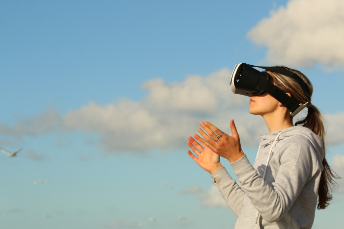 female with vr glasses over a blue sky