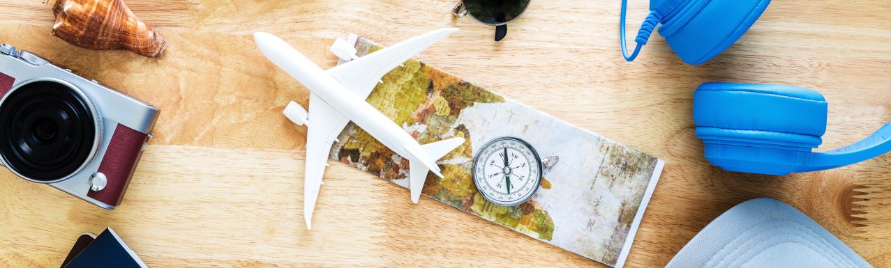 folded map with plastic airplane and compass on wooden table