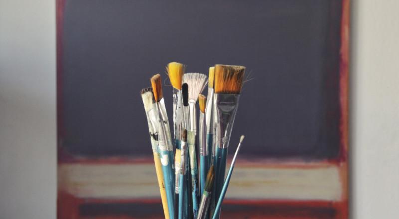 paintbrushes over blackboard