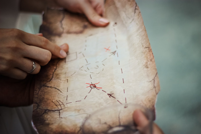 person holding a map drawn on brown paper