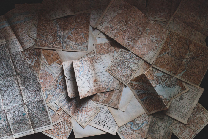 several old maps laying on a surface