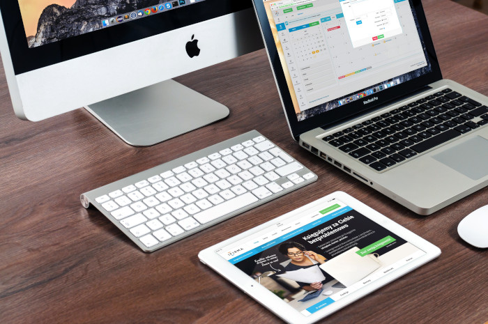 three apple devices opened on a wooden desk