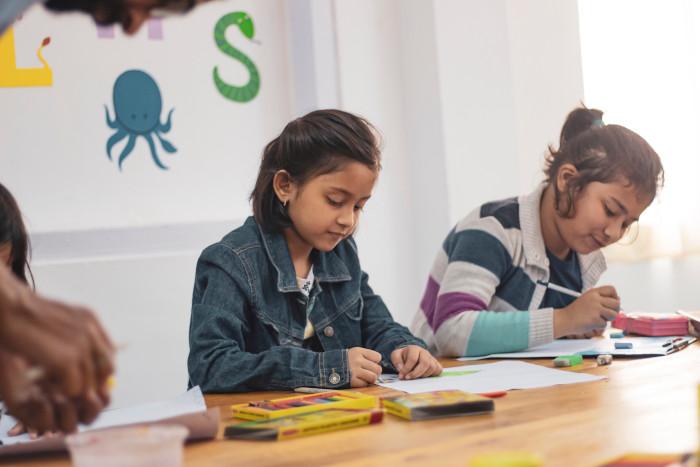 2 little girls writing in class